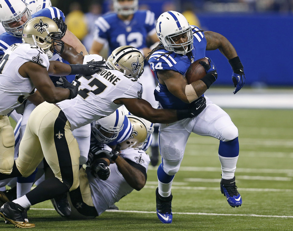 Photo - Indianapolis Colts running back Trent Richardson, right, breaks the tackle of New Orleans Saints inside linebacker David Hawthorne during the first half of an NFL preseason football game in Indianapolis, Saturday, Aug. 23, 2014. (AP Photo/Sam Riche)