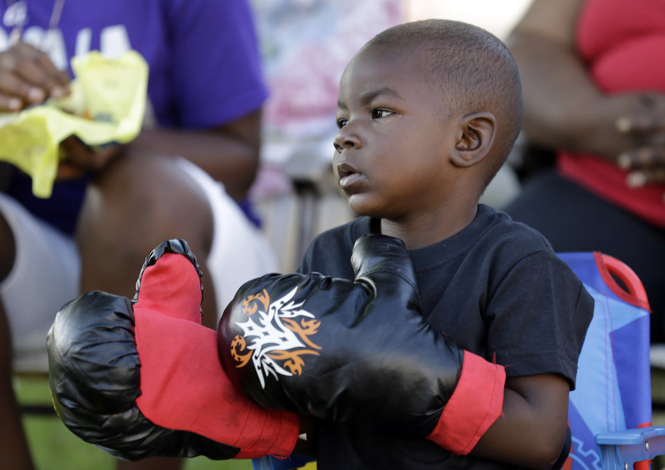 Photo - Tymetrius Steward, 3, wears boxing gloves to honor Muhammad Ali as he awaits his funeral procession to make its way down Muhammad Ali Boulevard in Louisville, Ky. Friday, June 10, 2016. (AP Photo/Michael Conroy)
