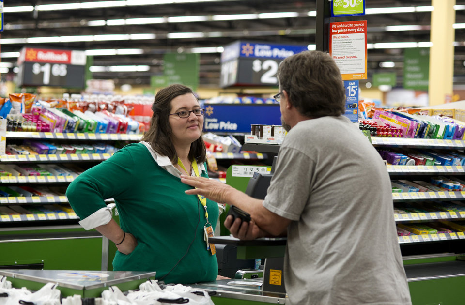 Photo - Wal-Mart cashier Candance Jones, left, speaks with customer Bill Watson, at Wal-Mart Neighborhood Market in Bentonville, Ark., Thursday, June 5, 2014. Wal-Mart's supercenters still account for 80 percent of its 4,000-plus U.S. stores, but the retailer is opening smaller outlets that cater to shoppers looking for more convenience. It now plans to open 270 to 300 small stores during the current fiscal year — double its initial forecast.  (AP Photo/Sarah Bentham)
