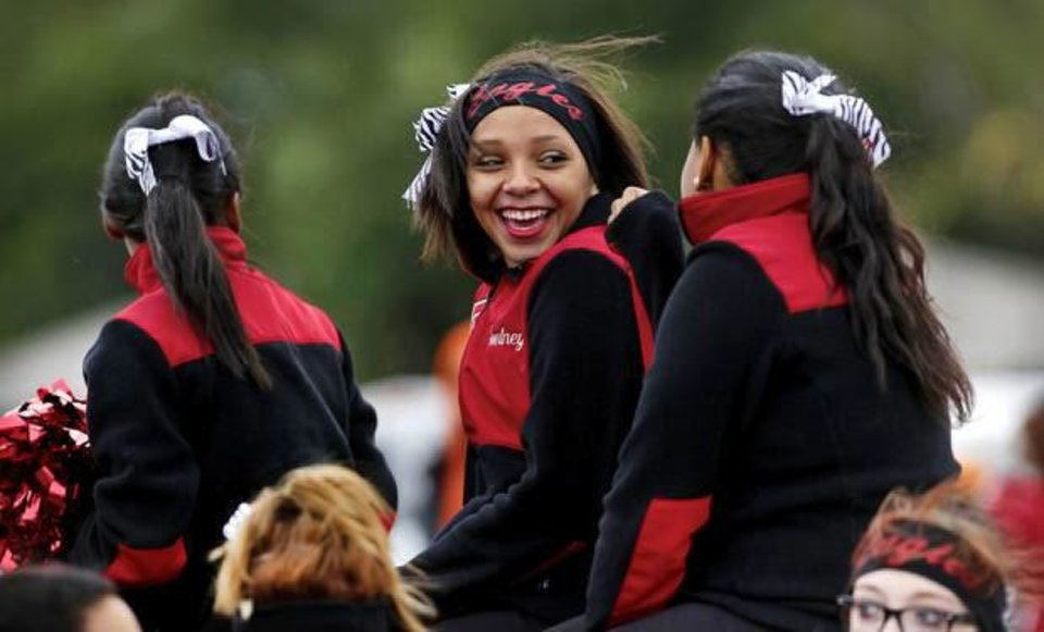 Photo - Freshman pom squad member Courtney Williams smiles as she looks back from her seat in the Del City High School  homecoming parade.   Photo by Jim Beckel,  The Oklahoman.
