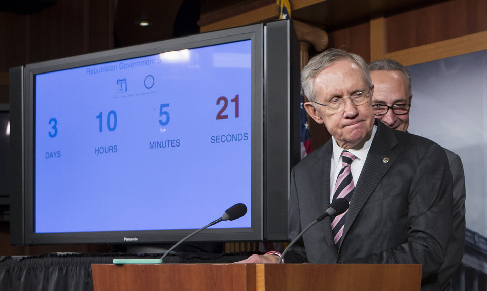 Photo - Senate Majority Leader Harry Reid of Nev., foreground, and Sen. Charles Schumer, D-N.Y. , stand next to a countdown clock indicating three days to go before the federal government is due to run out of money, Friday, Sept. 27, 2013, during a news conference on Capitol Hill in Washington, after passing a stopgap spending bill to keep the government running, but stripped of the defund