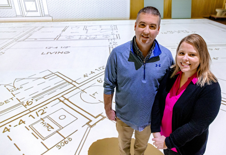 Photo - Projected Plans owners Brian and Angela Porch pose for a photo with a projection of life size blueprints at Projected Plans in Norman, Okla. on Tuesday, Sept. 29, 2020.  [Chris Landsberger/The Oklahoman]