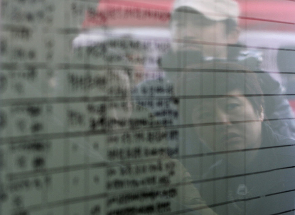Photo - Relatives of passengers aboard the sunken ferry Sewol are reflected on a board of the official list of the dead victims at a port in Jindo, South Korea, Monday, April 21, 2014. Divers continued the grim work of recovering bodies from inside the sunken South Korean ferry in the water off the southern coast Monday, as a newly released transcript showed the ship was crippled by confusion and indecision well after it began listing. The transcript suggests that the chaos may have added to a death toll that could eventually exceed 300. (AP Photo/Ahn Young-joon)