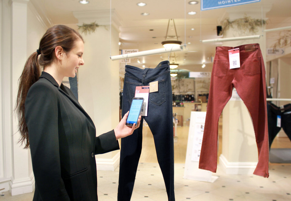 Photo -  In this undated photo provided by Hointer, a woman demonstrates the Seattle store's shopping technology. Hointer displays clothing not in piles or on racks but as one piece hanging at a time, like a gallery. Shoppers just touch their smartphones to a coded tag on the item and then select a color and size via their phone. Technology in the store keeps track of the items, and by the time a shopper is ready to try them on, they're already at the dressing room. AP Photo   Uncredited -  AP