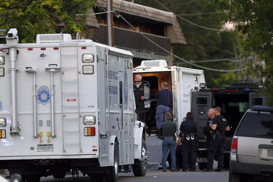 Photo - Police gather near an apartment house where the suspect in a shooting at a movie theatre lived in Aurora, Colo., Friday, July 20, 2012. As many as 14 people were killed and 50 injured at a shooting at the Century 16 movie theatre early Friday during the showing of the latest Batman movie. (AP Photo/Ed Andrieski) ORG XMIT: COEA108