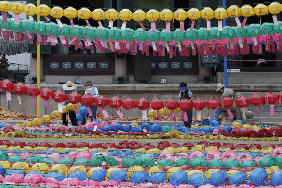 Photo -  Workers wearing face masks to help protect against the spread of the new coronavirus remove lanterns after celebrations of Buddha's birthday at the Chogyesa temple in Seoul, Monday, June 29, 2020. This year a ceremony to celebrate the birthday was put off from April 30 to May 30 due to the coronavirus. (AP Photo/Ahn Young-joon)