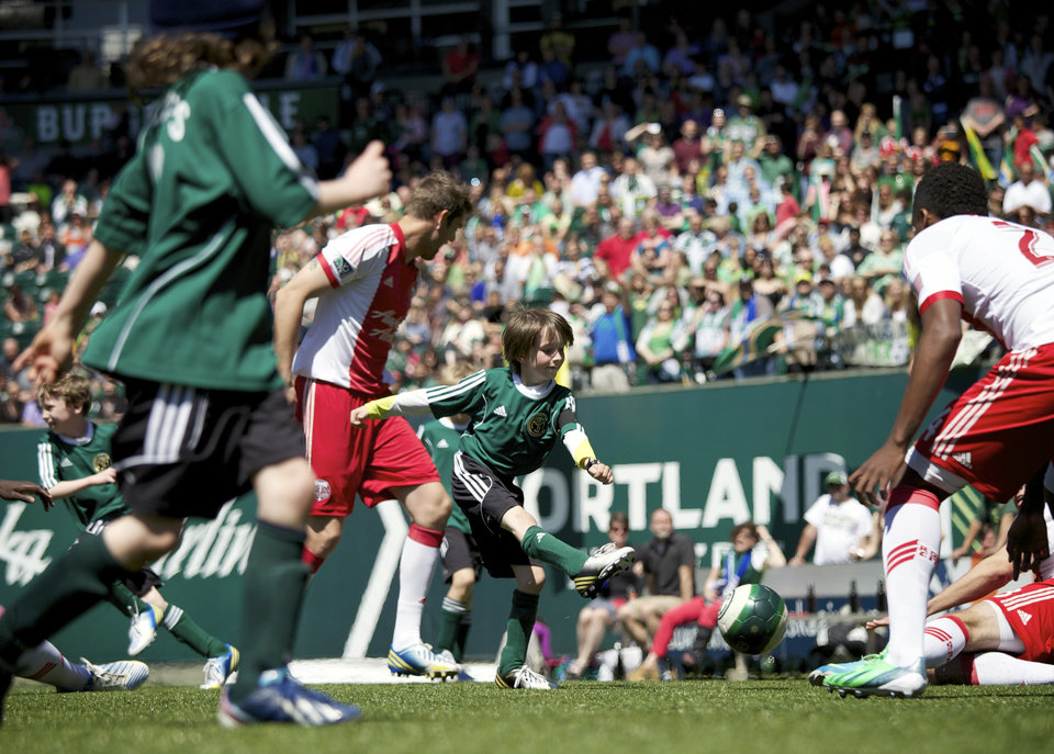 Photo - Atticus Lane-Dupre, 8, center, and his soccer team, The Green Machine, play the Portland Timbers soccer team in Portland, Ore., Wednesday, May 1, 2013. The Timbers and Make-A-Wish Oregon treated Atticus' team to a game at Jeld-Wen Field with more than 3,000 fans coming out to lend their support. Atticus missed the Green Machine's final match last fall because of cancer treatment. (AP Photo/The Oregonian, Bruce Ely)