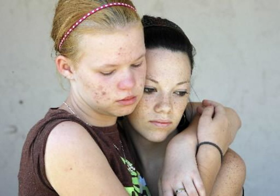 Photo - Junior Amber Shoebottom and Senior Tabitha Weaver hug each other at a fund-raiser to help the family of Taylor Paschal-Placker and Skyla Whitaker, who were shot and killed last Sunday on the dirt road near one of their homes, Tuesday, June 10, 2008. Photo by David McDaniel