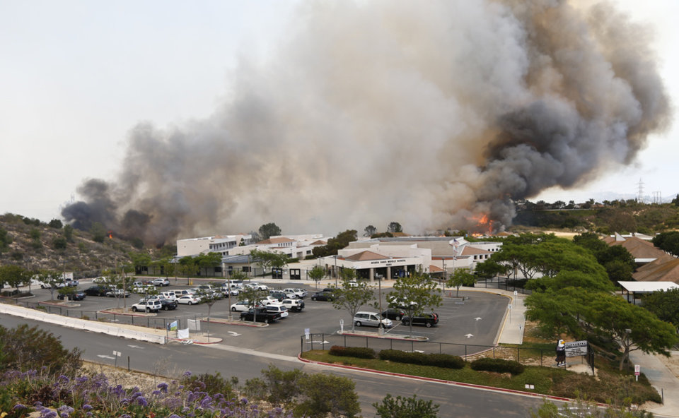 Photo - A wild fire burns toward a Aviara Oaks Middle School Wednesday, May 14, 2014, in Carlsbad, Calif.  Wind-driven flames are threatening homes in the coastal city of Carlsbad, where officials have sent mandatory evacuation notices to more than 11,000 homes and businesses. (AP Photo)