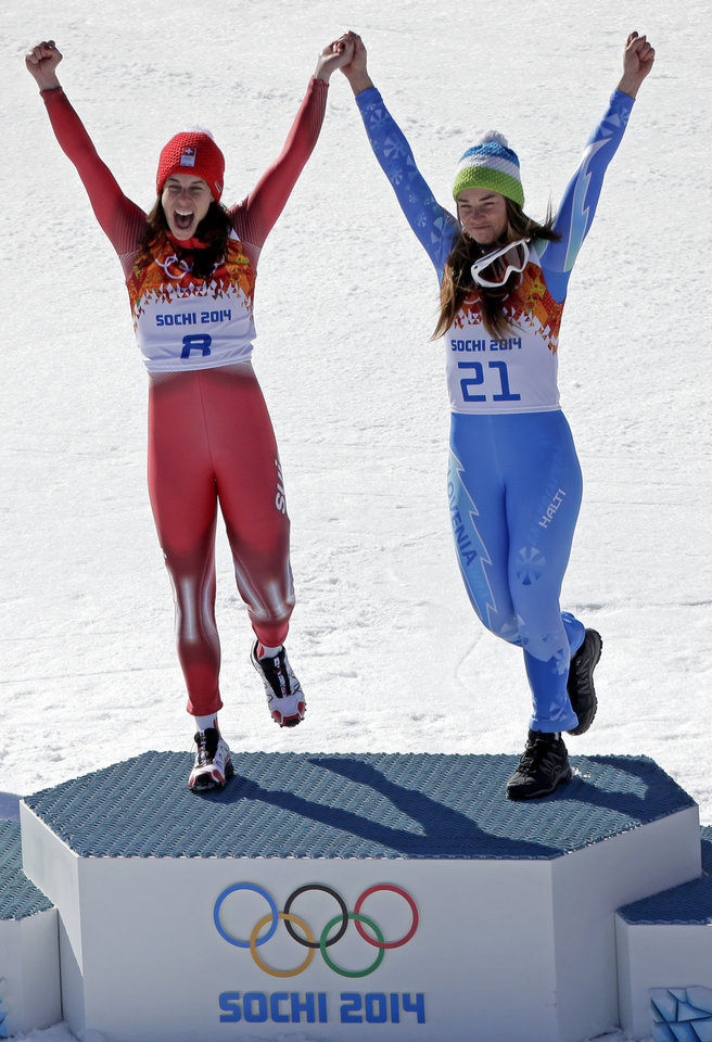 Photo - Women's downhill gold medal winners Switzerland's Dominique Gisin, left, and Slovenia's Tina Maze stand together on the podium during a flower ceremony at the Sochi 2014 Winter Olympics, Wednesday, Feb. 12, 2014, in Krasnaya Polyana, Russia. (AP  Photo/Charlie Riedel)