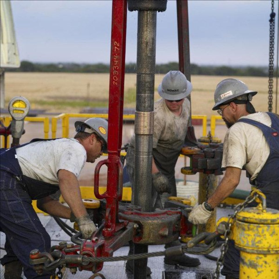 Workers with Chesapeake Energy Corp. subsidiary Nomac Drilling work on a rig near Oklahoma City in June 2007. - provided