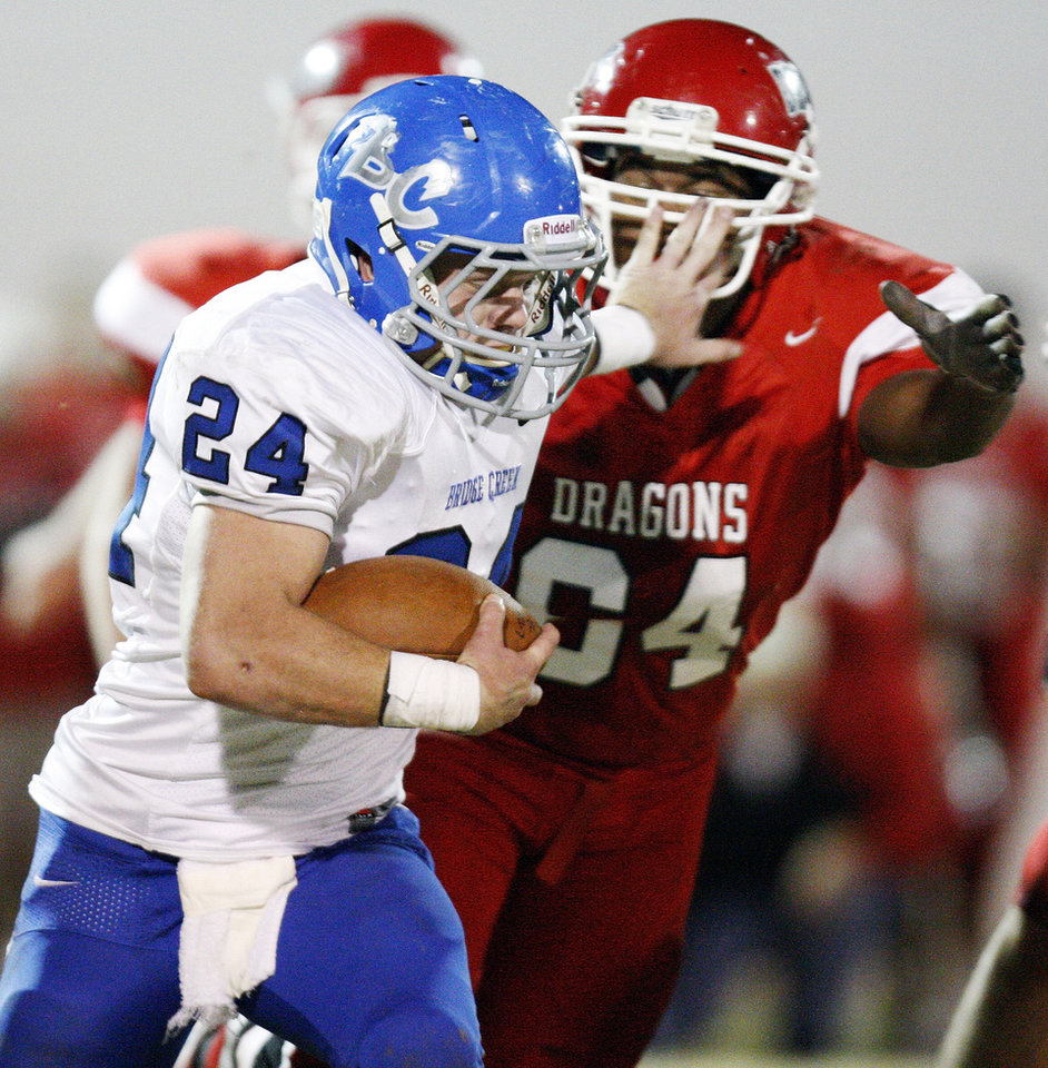 Photo - Bridge Creek's Chris Golden (24) tries to break away from Purcell's Cornell Haley (64) during a high school football playoff game between Purcell and Bridge Creek at Conger Field in Purcell, Okla.,Friday, Nov. 11, 2011. Photo by Nate Billings, The Oklahoman