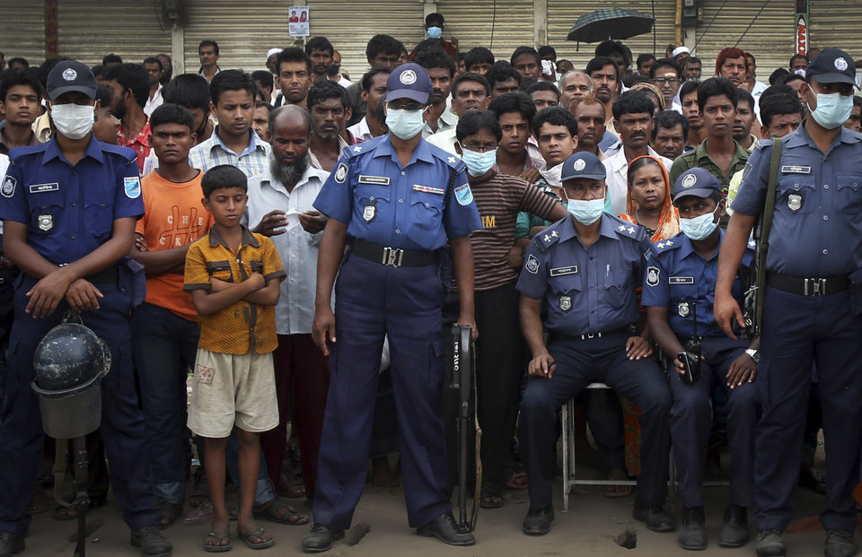 Photo - Policemen stand guard while a crowd gathers to watch workers toiling in a collapsed garment factory building on Tuesday, April 30, 2013 in Savar, near Dhaka, Bangladesh. Emergency workers hauling large concrete slabs from the collapsed eight-story building said Tuesday they expect to find many dead bodies when they reach the ground floor. (AP Photo/Wong Maye-E)