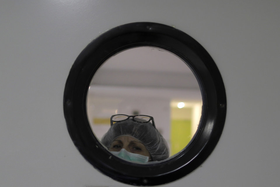 Photo -  A health worker wearing a face mask to protect from coronavirus, looks out of from a window at a nursing home in Madrid, Spain, Tuesday, March 31, 2020. The new coronavirus causes mild or moderate symptoms for most people, but for some, especially older adults and people with existing health problems, it can cause more severe illness or death. (AP Photo/Manu Fernandez)