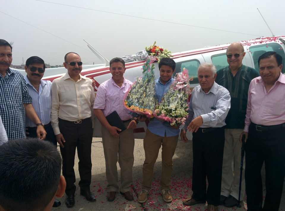 Photo - In a photo provided by Citizens Foundation, Haris Suleman, center right, in blue shirt, and his father, Babar Suleman, center left, stand with the plane in early July 2014 in Pakistan that they were flying on an around-the-world trip. Haris Suleman, 17, who was attempting to set a record for an around-the-world flight, was killed when his plane crashed in the Pacific Ocean, and crews were searching Wednesday, July 23, 2014, for his father, who was also on board. Family spokeswoman Annie Hayat said the plane flown by Haris Suleman went down shortly after leaving Pago Pago in American Samoa Tuesday night. Hayat said the body of Haris Suleman had been recovered, but crews were still looking for Babar Suleman. The father and son were using the trip to raise money for the Citizens Foundation, a nonprofit that builds schools in Pakistan. (AP Photo/Citizens Foundation)