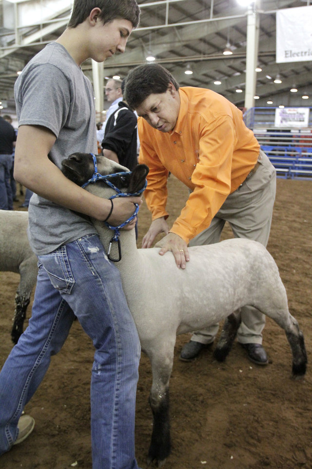 Photo - Sheep Superintendent Jerry Fitch works with Walters student Cooper Baumann and his sheep Thursday before the first round of judging at Oklahoma Youth Expo. Photo by Paul Hellstern, the Oklahoman
