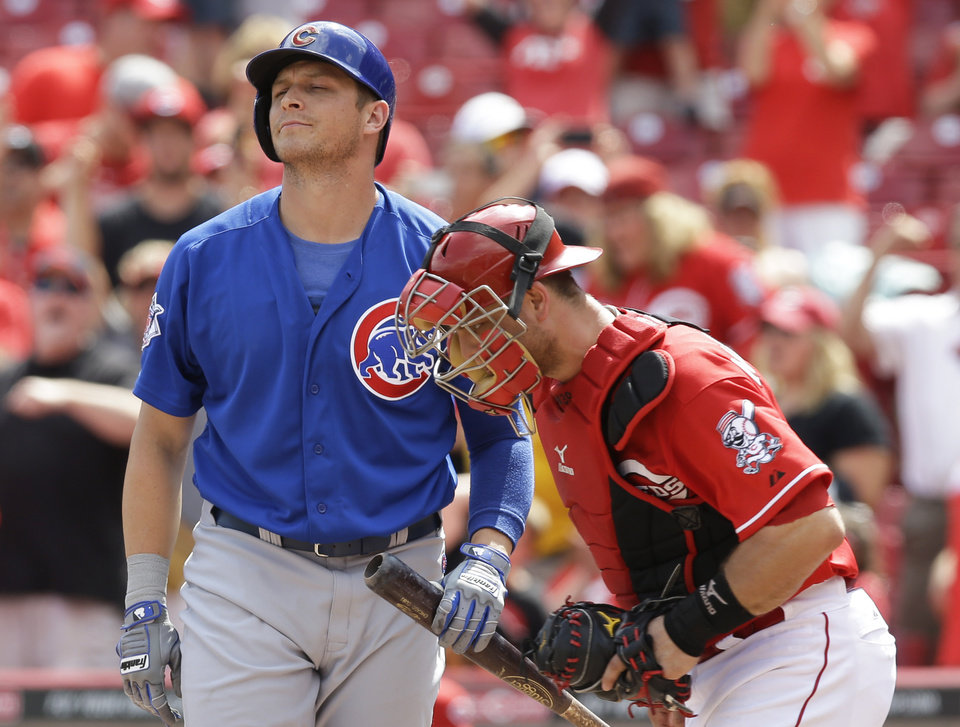 Photo - Chicago Cubs' Ryan Sweeney, left, strikes out against Cincinnati Reds relief pitcher Aroldis Chapman to end a baseball game, Tuesday, July 8, 2014, in Cincinnati. Catcher Devin Mesoraco runs to the mound at right. Cincinnati won 4-2. (AP Photo/Al Behrman)