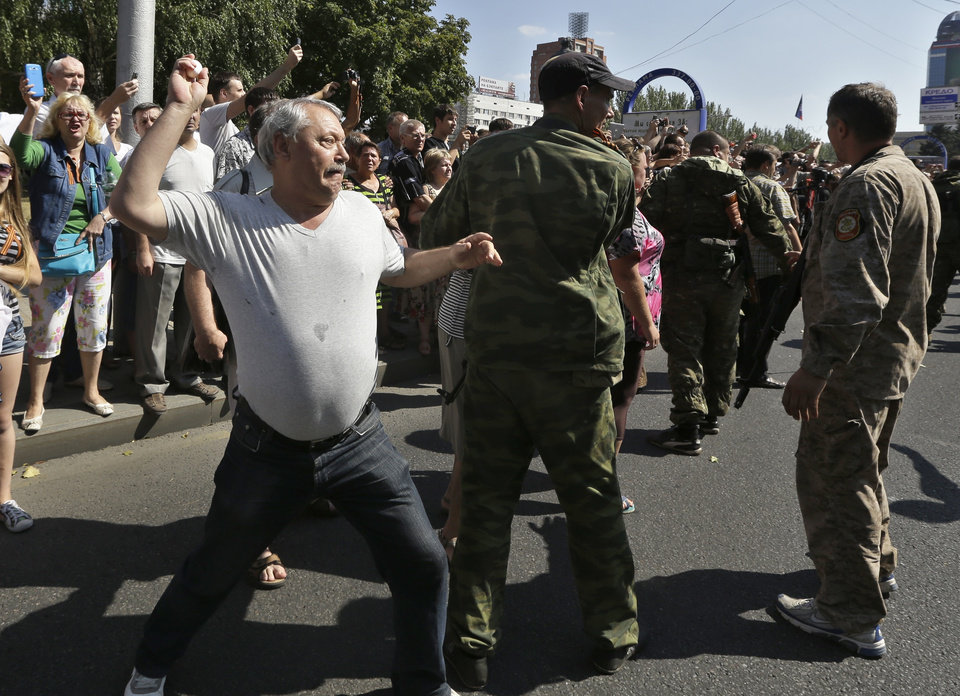Photo - A man throws an egg at captured Ukrainian army prisoners as they're escorted by Pro-Russian rebels in a central square in Donetsk, eastern Ukraine, Sunday, Aug. 24, 2014. Ukraine has retaken control of much of its eastern territory bordering Russia in the last few weeks, but fierce fighting for the rebel-held cities of Donetsk and Luhansk persists. (AP Photo/Sergei Grits)