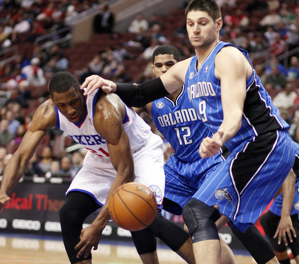 Photo - Philadelphia 76ers' Thaddeus Young, left, and Orlando Magic's Nikola Vucevic reach for the loose ball during the second half of an NBA basketball game on Wednesday, Feb 26, 2014, in Philadelphia. (AP Photo/Tom Mihalek)