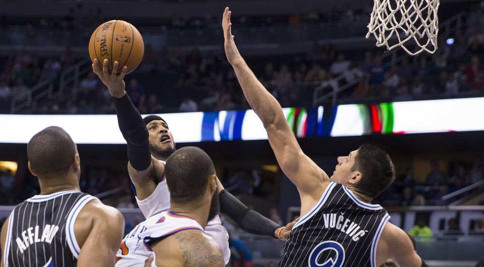 Photo - New York Knicks' Carmelo Anthony shoots against Orlando Magic's Nikola Vucevic (9) and Arron Afflalo, left, during overtime of an NBA basketball game in Orlando, Fla., Friday, Feb. 21, 2014. (AP Photos/Willie J. Allen Jr.)
