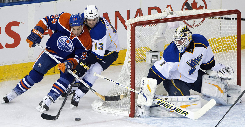 Photo - St. Louis Blues goalie Brian Elliott (1) makes the save as Carlo Colaiacovo (13) and Edmonton Oilers' Ryan Smyth (94) battle for the puck during the first period of an NHL hockey game in Edmonton, Alberta, on Saturday, Dec. 21, 2013. (AP Photo/The Canadian Press, Jason Franson)