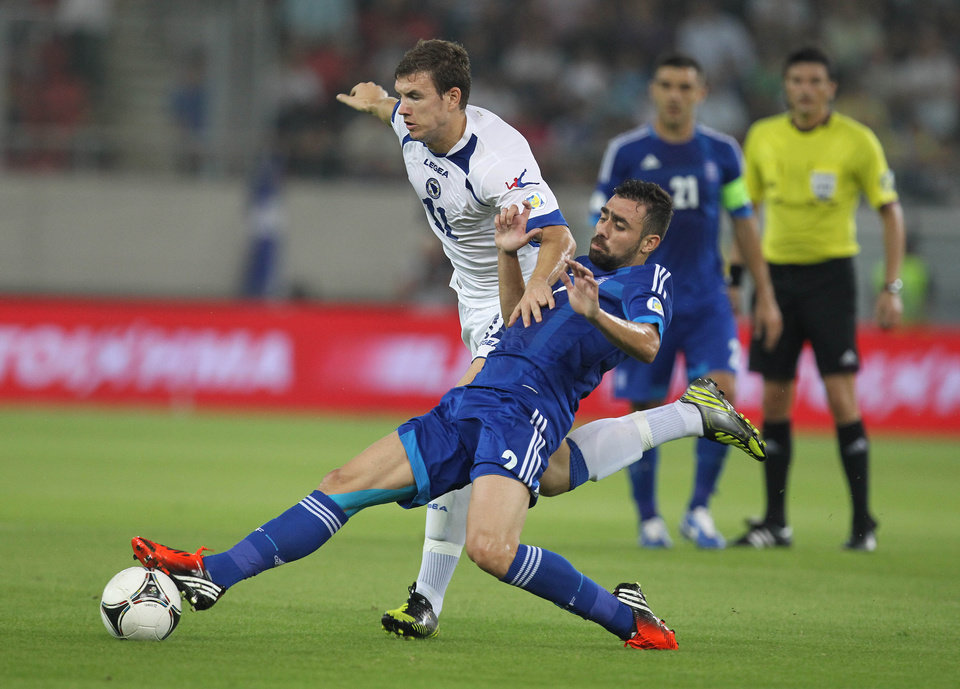 Greece's Giannis Maniatis, right, tries to stop Bosnia-Herzegovina's Edin Dzeko during their World Cup Group G qualifying soccer match at the Karaiskaki stadium in Piraeus port, near Athens, Thursday, Oct. 11, 2012. (AP Photo/Thanassis Stavrakis)