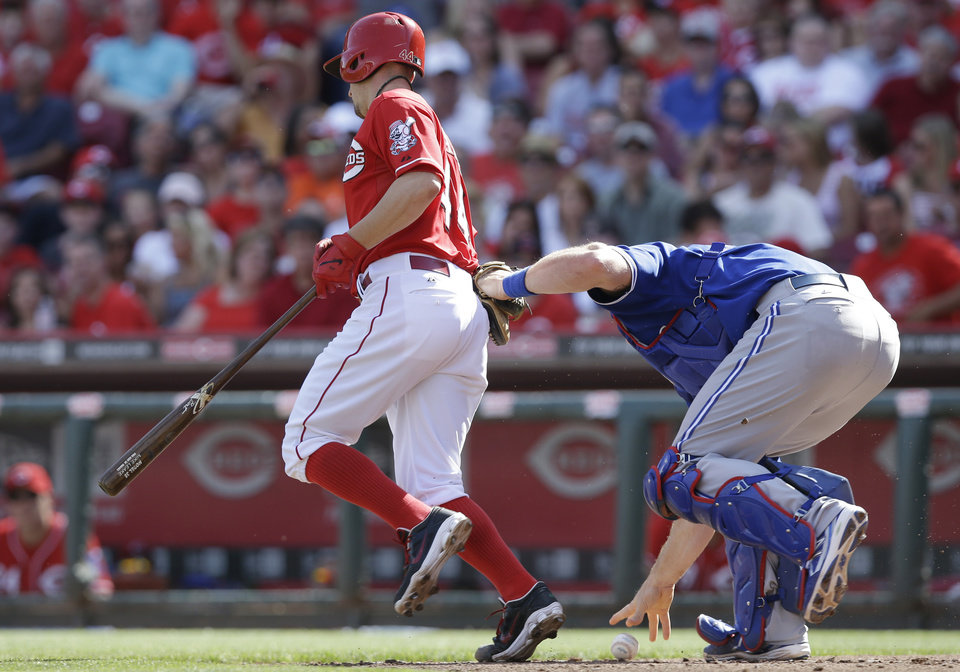 Photo - Toronto Blue Jays catcher Erik Kratz, right, fields a bunt by Cincinnati Reds' Mike Leake, left, that was ruled foul in the fourth inning of a baseball game on Saturday, June 21, 2014, in Cincinnati. (AP Photo/Al Behrman)