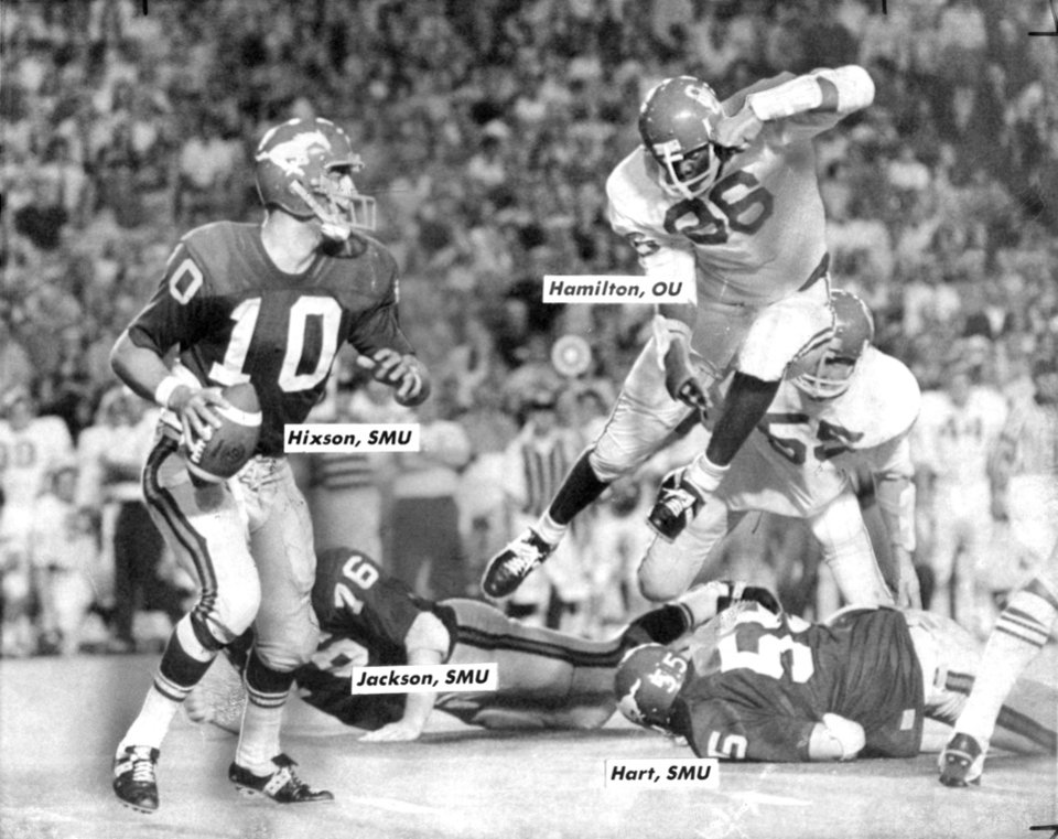 "FOOTBALL OU UNIVERSITY OF OKLAHOMA 1970 35.jpg: Caption reads ""OU defender Raymond Hamilton hurdles two would-be blockers and charges SMU passer Chuck Hixson."" Date photo was taken unknown. Photo was published in The Daily Oklahoman on 9-13-1970."