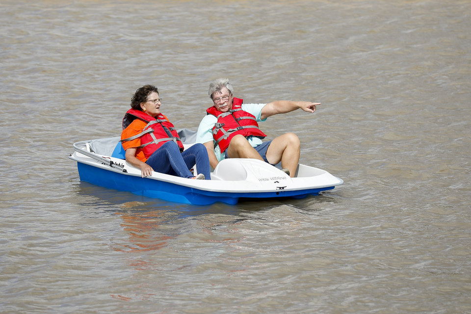 Photo - People enjoy a paddle boat ride on Scissortail Lake during the grand opening weekend of Scissortail Park in Oklahoma City, Sunday, Sept. 29, 2019. (Alonzo Adams for The Oklahoman)