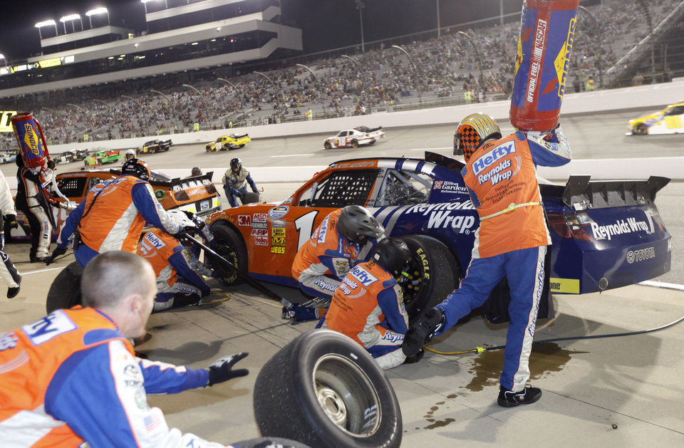 Photo -   Eric McClure (14) makes a pit stop during the NASCAR Nationwide Series auto race at Richmond International Raceway in Richmond, Va., Friday, Sept. 7, 2012. (AP Photo/Steve Helber)