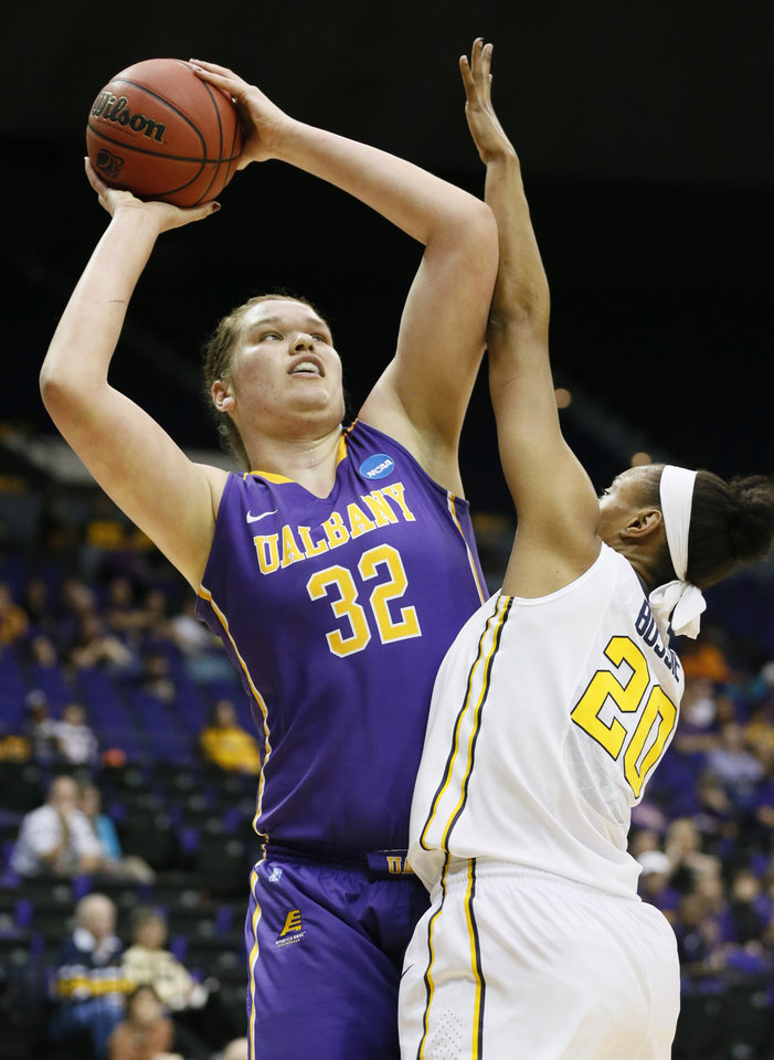 Photo - Albany center Megan Craig (32) attempts a shot at the basket while West Virginia center Asya Bussie (20) defends in the first half of an NCAA college basketball first-round tournament game on Sunday, March 23, 2014, in Baton Rouge, La. (AP Photo/Rogelio V. Solis)