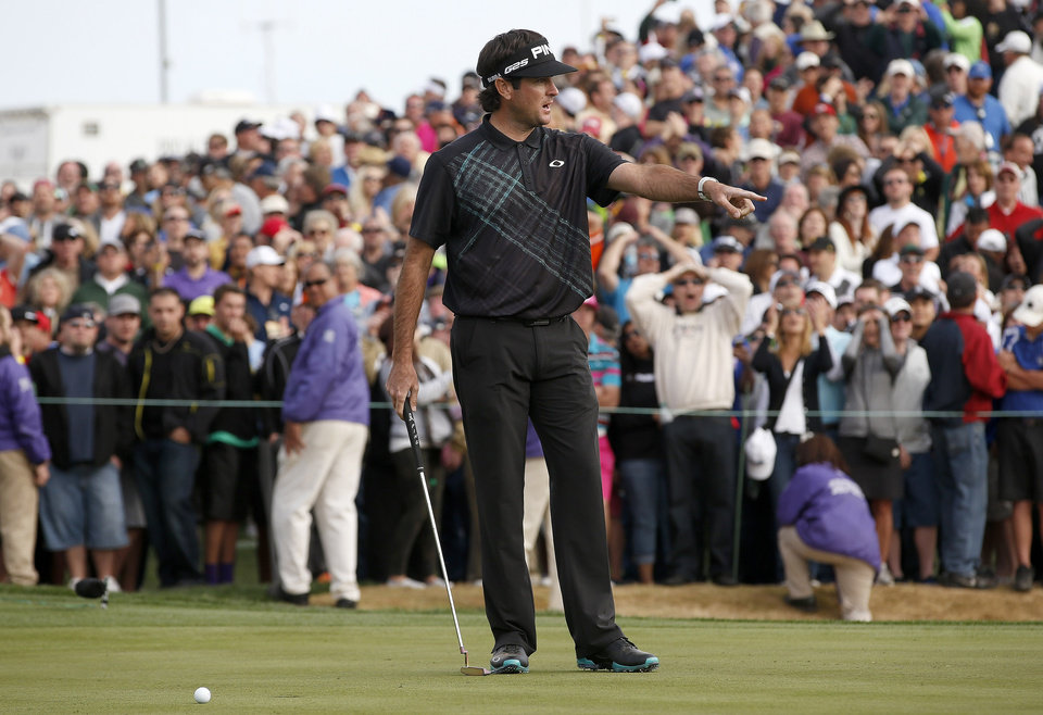 Photo - Bubba Watson talks to his caddie after missing a short putt on the 18th hole that would have forced a playoff during the final round of the Phoenix Open golf tournament on Sunday, Feb. 2, 2014, in Scottsdale, Ariz. Watson's missed putt allowed Kevin Stadler to earn the win. (AP Photo/Ross D. Franklin)