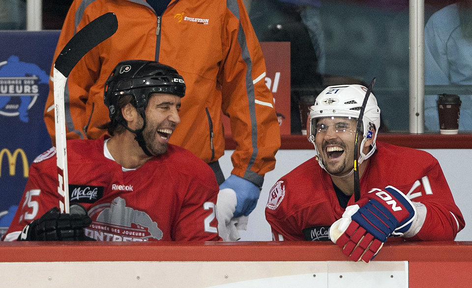 Photo -   Philadelphia Flyers' Maxime Talbot, left, and Montreal Canadiens' Brian Gionta laugh while sitting on the bench during the first period of a charity hockey game in Chateauguay, Quebec, Thursday, Sept. 27, 2012. The NHL canceled the rest of the preseason Thursday, just a day before negotiations were set to resume in an effort to end the lockout. (AP Photo/The Canadian Press, Graham Hughes)