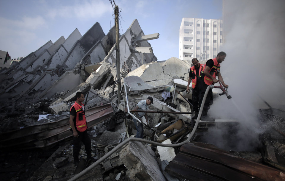 Photo - Palestinian firefighters extinguish a fire in the rubble of the destroyed 15-story Basha Tower, following early morning Israeli airstrikes in Gaza City, Tuesday, Aug. 26, 2014. Tuesday's strikes leveled the 15-story Basha Tower with apartments and offices and severely damaged another high-rise, the Italian Complex, built in the 1990s by an Italian businessman, with dozens of shops and offices. (AP Photo/Khalil Hamra)