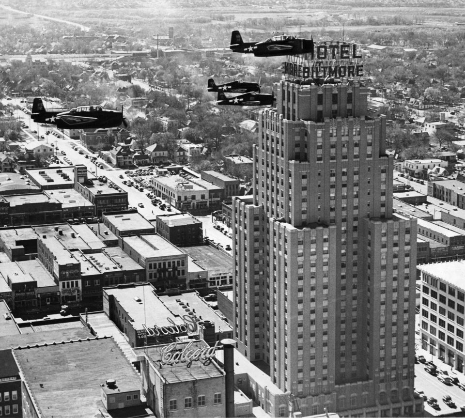 OKLAHOMA CITY / SKY LINE / OKLAHOMA / AERIAL VIEWS / AERIAL PHOTOGRAPHY / AIR VIEWS:  BUZZ-Z-Z! There are two ways to reach a hotel room.  No.1, ride up on the elevator.  No. 2, pick your floor and just Hellcat through a window.  Most of downtown Oklahoma Cityans thought Friday afternoon that the visiting naval aviators were using system No. 2 - and that includes Morris Sparlin, Daily Oklahoman phtoographic chief, who brought along this picture to prove that Beacon club luncheon guests had to lean over the railing to see those two TBMs and a couple F6Fs going down Grand avenue without even a pause for traffic lights.  They were calling attention to the Victory loan drive.  And that they did.  Staff photo by Morris E. Sparlin.  Photo dated 11/23/1945 and published on 11/24/1945 in The Daily Oklahoman.