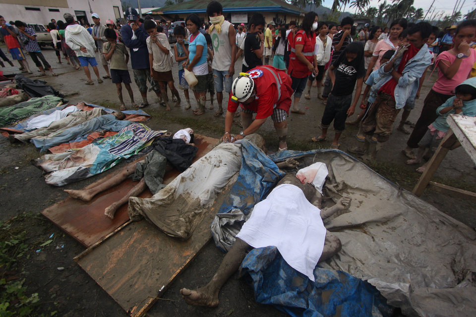 Photo - A rescuer covers bodies recovered from flashflood in New Bataan, Compostela Valley province, southern Philippines Wednesday, Dec. 5, 2012. The death toll from Typhoon Bhopa climbed to more than 100 people Wednesday, while scores of others remain missing in the worst-hit areas of the southern Philippines. (AP Photo/Karlos Manlupig)
