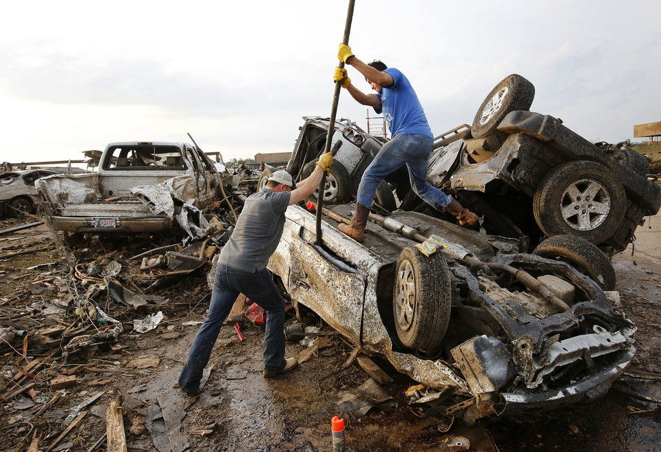 Two men attempt  to pry open a door on this car to check for victims in a business parking lot west of I-35 south of 4th Street  in Moore, on Monday, May 20, 2013.    Photo  by Jim Beckel, The Oklahoman.