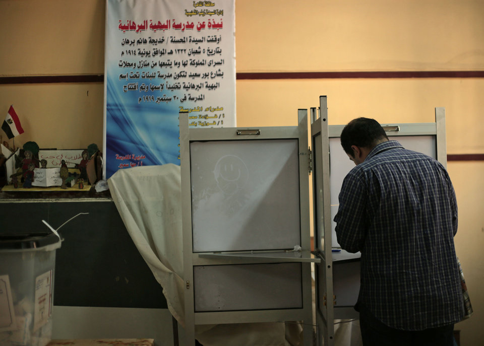 Photo - A man votes during the second day of voting in the presidential election, in Cairo, Egypt, Tuesday, May 27, 2014. State TV says Egypt's election commission has extended voting in the presidential election for a third day amid reported low turnout. Government officials, media and the military harangued voters to go to the polls Tuesday in what was supposed to be the final day of the vote, worried that turnout was weaker than expected. The front-runner, former army chief Abdel-Fattah el-Sissi, is trying to garner an overwhelming show of support. (AP Photo/Nariman El-Mofty)