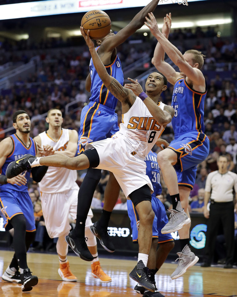 Photo - Phoenix Suns guard Tyler Ulis (8) slips between Oklahoma City Thunder forwards Kyle Singler, right, and Jerami Grant during the second half of an NBA basketball game, Friday, April 7, 2017, in Phoenix. The Suns won 120-99. (AP Photo/Matt York)