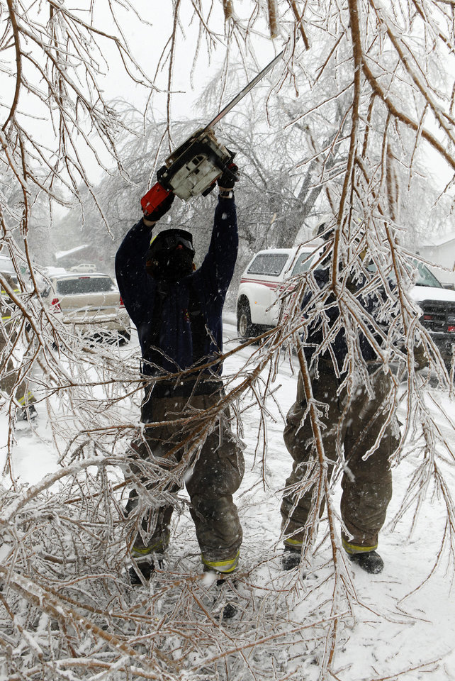 Photo - Purcell firefighter Jason Benefiel cuts limbs obstructing traffic on city streets on Friday, Jan. 29, 2010, in Purcell, Okla. after a winter storm.  Photo by Steve Sisney, The Oklahoman