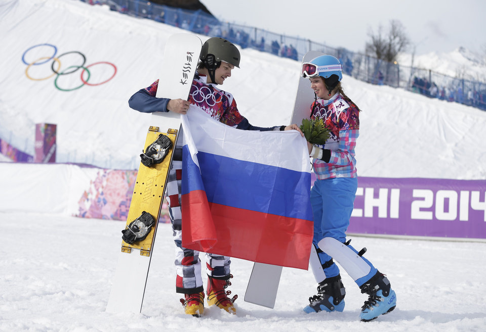 Photo - Men's snowboard parallel giant slalom gold medalist Vic Wild of Russia, left, celebrates with his wife and bronze medalist in the women's snowboard parallel giant slalom final, Russia's Alena Zavarzina, at the Rosa Khutor Extreme Park, at the 2014 Winter Olympics, Wednesday, Feb. 19, 2014, in Krasnaya Polyana, Russia.  (AP Photo/Andy Wong)
