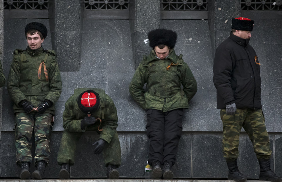 Photo - Cossacks guard the regional parliament building during the Crimean referendum in Simferopol, Ukraine, Sunday, March 16, 2014. Residents of Ukraine's Crimea region are voting in a contentious referendum on whether to split off and seek annexation by Russia. (AP Photo/Vadim Ghirda)