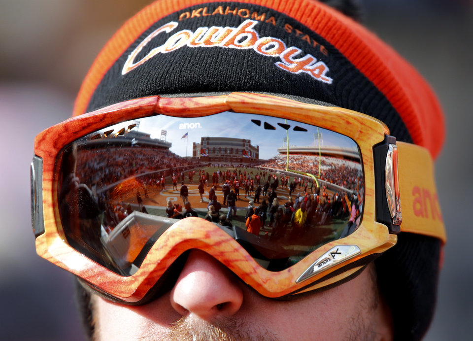 Photo - An Oklahoma State fan wears goggles to brave the cold during the Bedlam college football game between the Oklahoma State University Cowboys (OSU) and the University of Oklahoma Sooners (OU) at Boone Pickens Stadium in Stillwater, Okla., Saturday, Dec. 7, 2013. Photo by Chris Landsberger, The Oklahoman