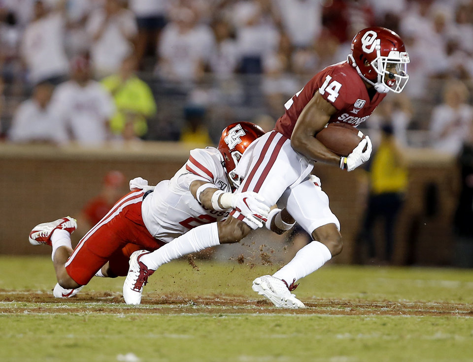 Photo - Oklahoma's Charleston Rambo (14) is tackled by Houston's Gleson Sprewell (21) during a college football game between the University of Oklahoma Sooners (OU) and the Houston Cougars at Gaylord Family-Oklahoma Memorial Stadium in Norman, Okla., Sunday, Sept. 1, 2019. [Sarah Phipps/The Oklahoman]