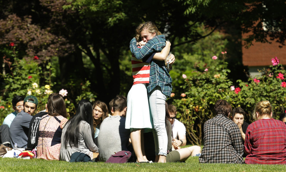 Photo - Two women embrace near a prayer circle on the campus of Seattle Pacific University, Friday, June 6, 2014 in Seattle. Classes were canceled Friday following a shooting at Otto Miller Hall Thursday afternoon.   A 19-year-old man was fatally shot and two other young people were wounded after a gunman entered the foyer  and started shooting.  Aaron R. Ybarra, 26, was booked into the King County Jail late Thursday for investigation of homicide, according to police and the jail roster. (AP Photo/Ted S. Warren)