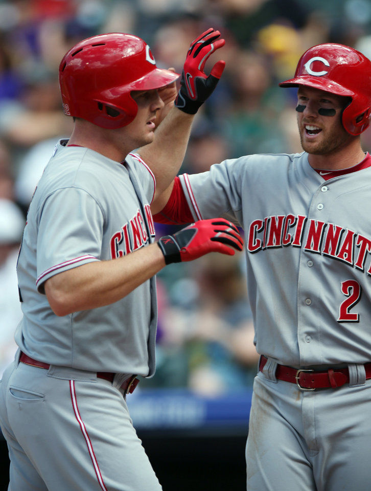 Photo - Cincinnati Reds' Jay Bruce, left, is congratulated after hitting a two-run home run by teammate Zack Cozart against the Colorado Rockies in the fourth inning of a baseball game in Denver on Sunday, Aug. 17, 2014. (AP Photo/David Zalubowski)