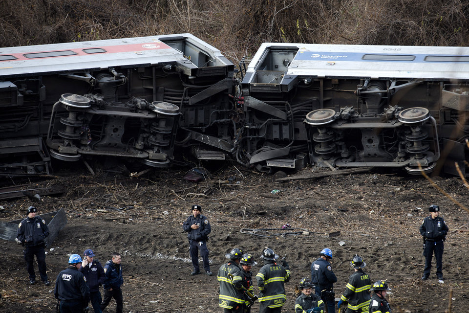 Photo - Emergency personnel respond to the scene of a Metro-North passenger train derailment in the Bronx borough of New York Sunday, Dec. 1, 2013. The train derailed on a curved section of track in the Bronx on Sunday morning, coming to rest just inches from the water and causing multiple fatalities and dozens of injuries, authorities said. Metropolitan Transportation Authority police say the train derailed near the Spuyten Duyvil station. (AP Photo/John Minchillo)