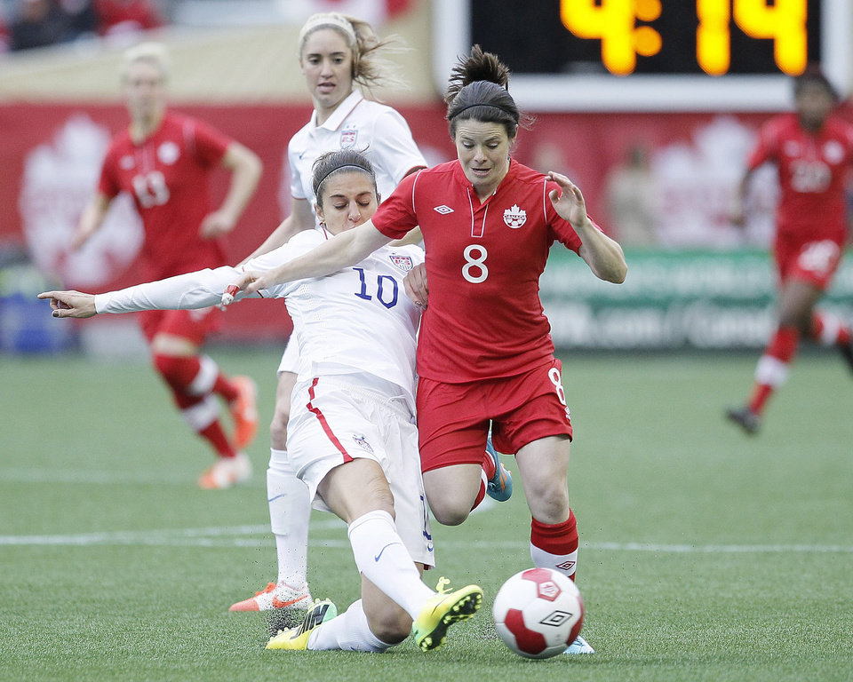 Photo - United States midfielder Carli Lloyd (10) knocks the ball away from Canada midfielder Diana Matheson (8) during first half of an exhibition soccer match in Winnipeg, Manitoba, Thursday, May 8, 2014. (AP Photo/The Canadian Press, John Woods)