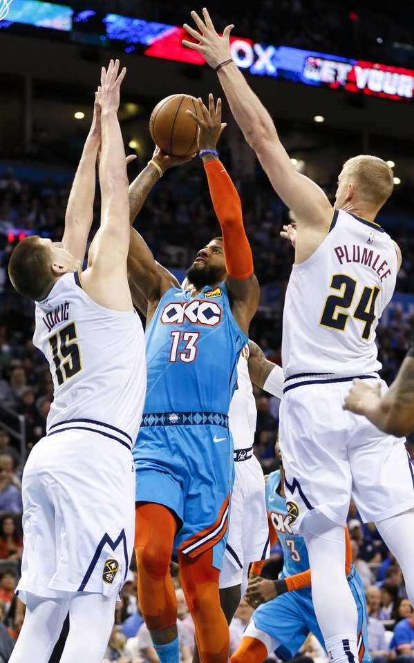 Photo - Oklahoma City's Paul George (13) shoots between Denver's Nikola Jokic (15) and Mason Plumlee (24) during an NBA basketball game between the Denver Nuggets and the Oklahoma City Thunder at Chesapeake Energy Arena in Oklahoma City, Friday, March 29, 2019. Photo by Nate Billings, The Oklahoman