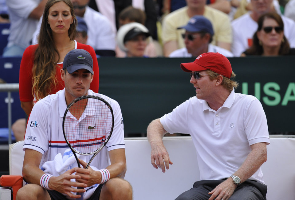 Photo -   John Isner of US, left, listens to his Davis Cup manager Jim Courier during the Davis Cup World Group semifinal tennis match against Spain's David Ferrer, in Gijon, northern Spain, Sunday, Sept. 16, 2012. Ferrer won 6-7, 6-3, 6-4, 6-2. (AP Photo/Alvaro Barrientos)